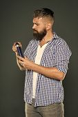 The Best Shampoo For His Hair. Bearded Man Holding Shampoo Bottle On Grey Background. Hipster With B poster