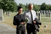 Bearded Senior Man Walking Near Woman With Flowers On Funeral poster