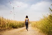 Woman In Countryside With Windmills. Lifestyle Concept. Hipster Woman Walking In Countryside With Wi poster