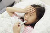 Asian Child Girl Is Sick And Has A Thermometer In Her Mouth While Lying On The Bed.  Sick Child With poster