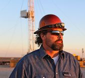 stock photo of oil derrick  - Oil and natural gas field worker watching the sunset - JPG