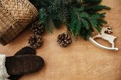 Reindeer Toy, Gloves, Basket With Fir Branches And Cones On Rustic Wooden Background. Flat Lay. Wint poster