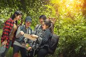 Group Of Young Friends Hiking In Autumn Colorful Forest, Looking At Map And Planning Hike. poster