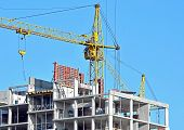 stock photo of social housing  - Building crane and building under construction against blue sky - JPG