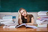 Frustrated Female Student Sitting At The Desk With A Huge Pile Of Study Books In Classroom. Young Co poster