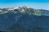 Top View Of The Mountain Range And Peaks Covered With Snow. Mountain Peak In The Summer. poster