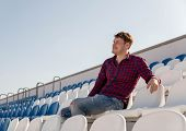 A Young Handsome Man In Plaid Shirt And Jeans Sits On A Stadium Bleachers Alone, Smiles And Looks Aw poster