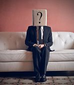 stock photo of incognito  - businessman sitting on sofa with head in box - JPG