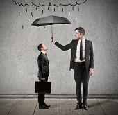 businessman with umbrella protects from rain another man