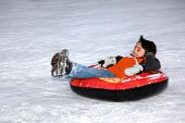 Boy Tubing Down Snowy Hill.