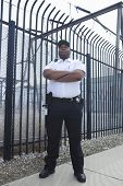 Security guard standing with arms crossed outdoors