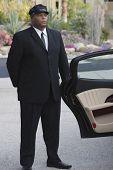 Mixed race chauffeur opening door of luxury car