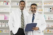 Portrait of a middle aged male pharmacist holding clipboard standing with coworker at workplace