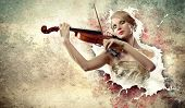 Image of beautiful female violinist playing with closed eyes against splashes background