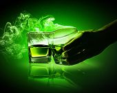 foto of absinthe  - Hand holding one of two glasses of green absinthe with fume going out - JPG