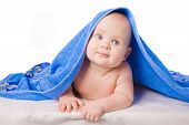 A beautiful baby under a blue towel