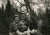 Vintage photo of parents with little son in forest (early eighties)