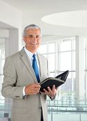 Portrait of a middle aged businessman standing in a modern office. Man is holding a small binder and