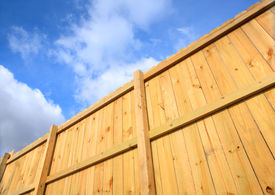 foto of wooden fence  - a wooden fence cuts diagonally across the screen with a blue sky and white puffy clouds - JPG