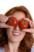 Pretty Red-haired Woman Holding Tomatoes Before Eyes
