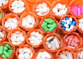 Looking down on a large group of prescription medicine bottles. The bottles all have their caps off and have a variety of drugs, tablets and capsules. Horizontal format filling the frame.
