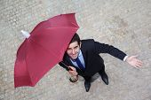 Confident businessman with umbrella checking if it's raining