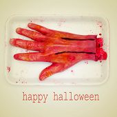 picture of a scary amputated hand and the sentence happy halloween on a beige background, with a retro effect