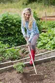 Blonde woman working with a rake in her garden