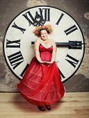 Funny Queen in red dress posing with clock