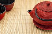 Japanese tetsubin and tea cups on a bamboo mat - a traditional cast iron red hobnail design with bla