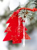 red christmas tree toy in snow with icicle