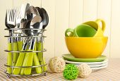 Kitchen cutlery in metal stand with clean dishes on tablecloth on beige background