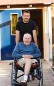 stock photo of amputation  - Old father being pushed in his wheelchair by his son - JPG
