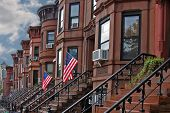 stock photo of brownstone  - Brownstone row houses in Sunset Park neighborhood of Brooklyn with cement stair entries  - JPG