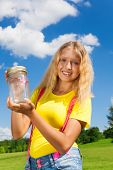 picture of 13 year old  - Happy 13 years old blond girl holding glass jar with butterfly standing in the park on sunny summer day - JPG