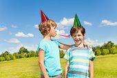 picture of prank  - Two boys on birthday party having fun with blowing into noisemaker loudly standing together in the park - JPG
