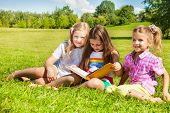 picture of three sisters  - Three happy girls sisters sitting in the grass in park together and reading a big yellow book