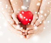 family, charity, healthcare, health. christmas, x-mas and happy people concept - woman and man hands with heart