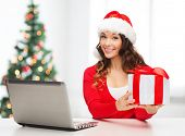 christmas, x-mas, online shopping concept - woman in santa helper hat with gift box and laptop compu