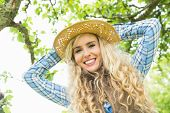 Beautiful blonde woman wearing a straw hat looking at the camera