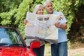 Smiling mature couple by their cabriolet reading map looking for direction