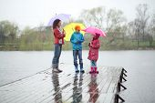 Mother and two children standing in the rain on a wooden pier