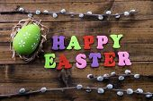 Easter egg in nest, pussy-willow and sign on color wooden background