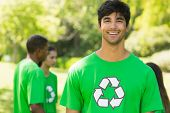 Portrait of a smiling young man wearing green recycling t-shirt in the park