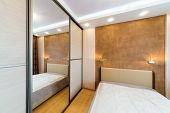 Modern bedroom with closet and large mirror