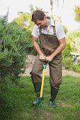 stock photo of dungarees  - Full length of a young man in dungarees raking the garden - JPG