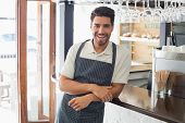 Portrait of a smiling confident young waiter standing at the cafe counter