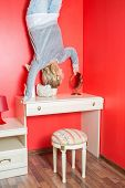 Girl upside down in the bedroom above the dressing table