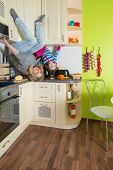 Mother and daughter sitting at shelves upside down in the colored kitchen