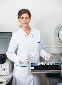 Portrait of female researcher with samples for coagulation analysis in lab